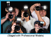 Tight group of photographers with using flash cameras. (Staged with professional models).