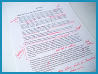 Draft of a news article covered with red editor marks and notes.