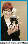 Red-headed woman with black glasses holding a trophy (staged with a professional model).