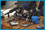Table covered with a variety of microphones and recording devices.