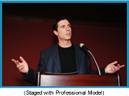 Man speaking at a podium gesturing with his hands (staged with a professional model).