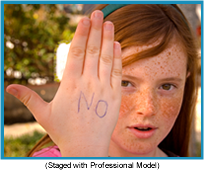 "Red-headed girl with her right hand in front of her with the word ""no"" written on it in blue (staged with professional model)."