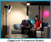 TV studio with two people sitting on a couch highlighted by floodlight. (Staged with professional models.)