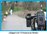 Cameraman in an outdoor venue with out of focus background. (Staged with profesisonal model).