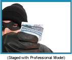 Man wearing ski hat, black mask, and gloves holding social security and credit cards.  (staged with professional model).