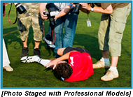 Press photographers taking pictures of an injured man laying on the ground holding his leg. (Photo staged with professional models).