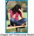 Woman sitting crosslegged on park bench with her head in her hands.