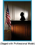 Silhouette of man in witness box in a courtroom with American flag on floor pole.