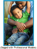 African-American father hugging son. (Staged with professional models).